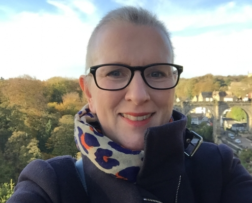 Harriet with some hair regrowth, wearing glasses, navy coat and leopard print scarf. Knareborough acquaduct in the background