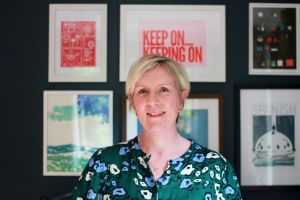 Harriet Mason in her office. Blonde hair, green floral patterned dress against a navy wall and brightly coloured pictures