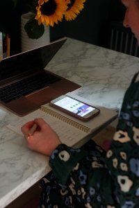 Harriet sat her desk, with phone, notebook, pen in hand, sunflowers and Mac