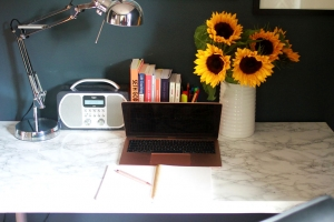 Harriet's desk with Mac, white jug of sunflowers, stack of marketing books, angle poise lamp, radio, notebook and pen
