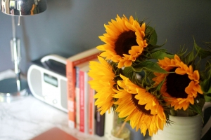Harriet's desk showing jug of sunflowers, row of books, radio and angel poise lamp