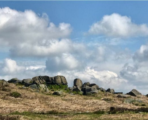 Cow and calf rocks at Ilkley Moor against a blue sky with white clouds