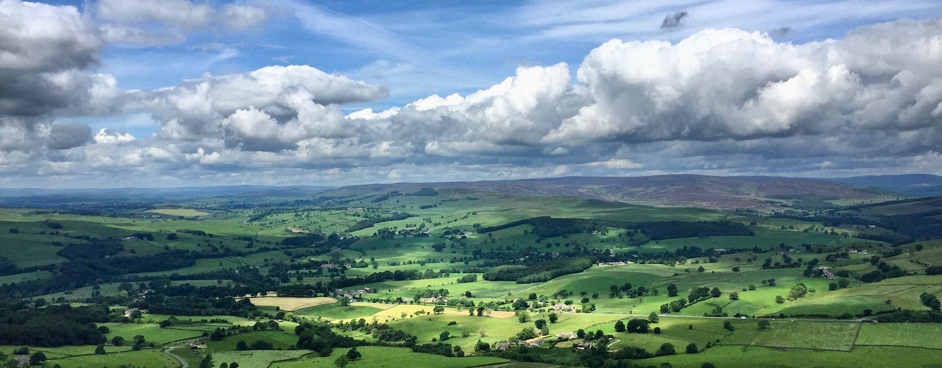 Views of the Yorkshire Moors from Beamsley Beacon. Dramatic cloudy sky, lots of green fields, trees and moorland in the distance.