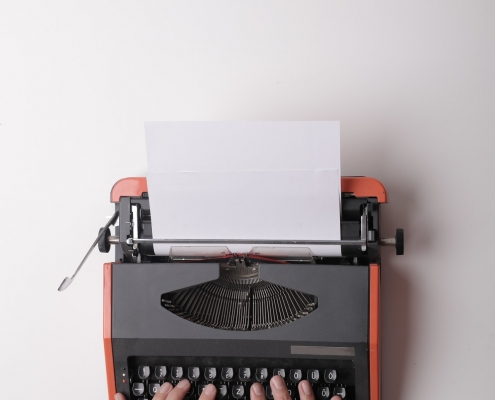 Old fashioned typewriter with blank sheet of paper and someone's hands ready to start typing