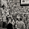 Black and white image of a busy, crowded indoor market.
