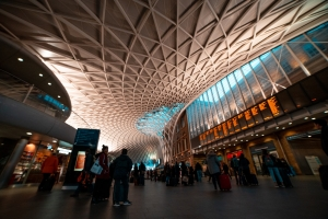 Kings Cross Railway station showing the criss cross pattern curved ceiling and people watching the arrivals board.