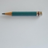 Short, sea green coloured sharpened pencil on a blank sheet of paper