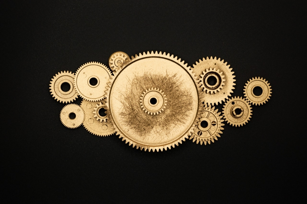 Brass worn cogs of different sizes against a black background