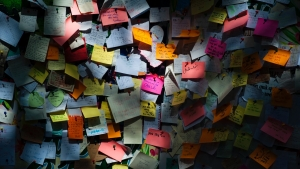 Wall covered in multi coloured post-it notes with notes scribbled on them