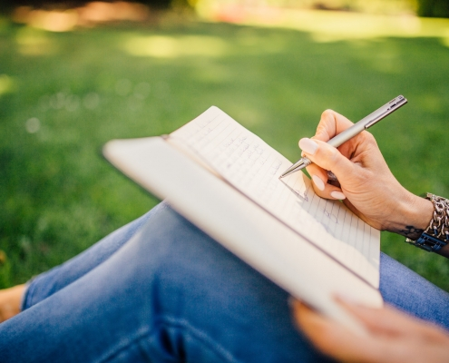 Woman sat on the grass writing in a notebook