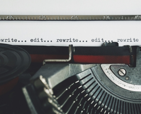 Close up of a vintage typewriter and ribbon with the type written words write, edit, rewrite