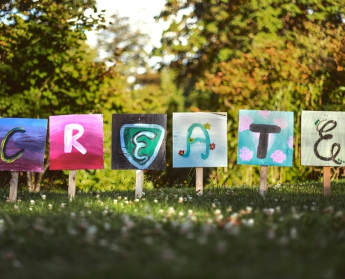 The word Create spelled out on individual cards in a garden setting